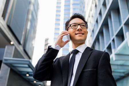 phone professional: Businessman in city holding his mobile Stock Photo