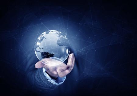 manos entrelazadas: La mano del hombre sosteniendo el planeta Tierra digital que representa el concepto global de tecnologías