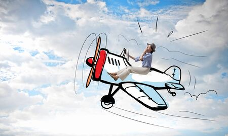 atop: Young funny woman flying in air in drawn airplane
