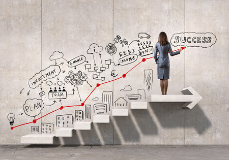 success strategy: Businesswoman drawing strategy plan over ladder leading to success Stock Photo