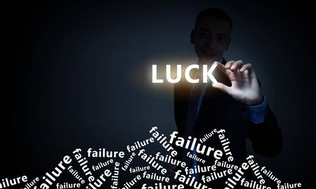 bad fortune: Businessman on dark background taking with fingers word luck