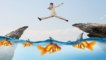 Concept of fake threat when businessman jumping over water gap with shark appear to be goldfish