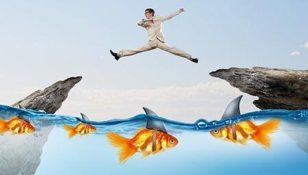 pez dorado: Concepto de amenaza falsa cuando el empresario saltando por encima de brecha de agua con tiburones parecen ser peces de colores