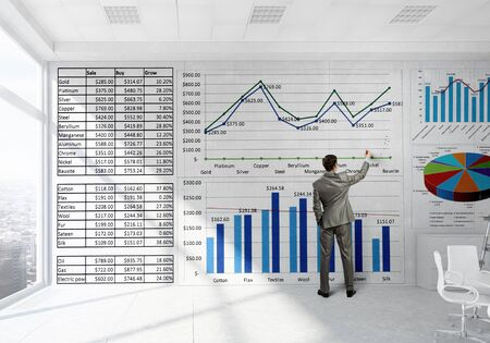 average guy: Back view of elegant businessman against modern ofiice window drawing infographs