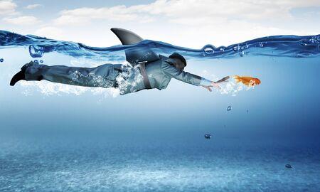 Jeune homme d'affaires avec le requin nageoire swiming sous l'eau