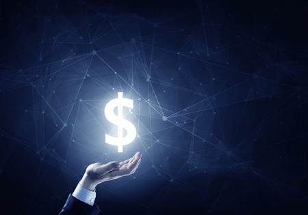 business sign: Businessman hands on dark background holding glowing dollar sign