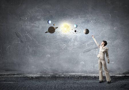 Jeune femme d'affaires main tendue aux planètes de l'espace Banque d'images