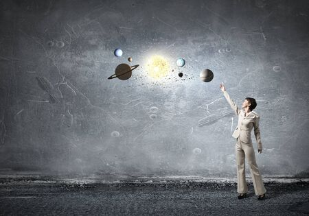 Young businesswoman reaching hand  to space planets Stock Photo