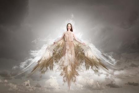 Aantrekkelijke vrouw met engelenvleugels op hemelachtergrond