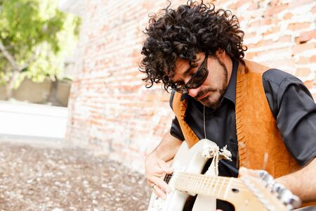 tuning: A street musician tuning his instrument Stock Photo