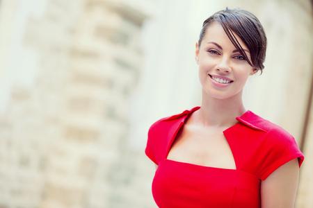 Retrato de mujer de negocios hermosa en el vestido rojo
