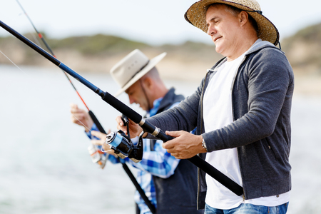 botas altas: Imagen de los pescadores que pescan con ca�as