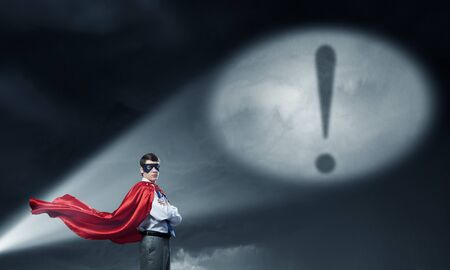 Young confident super businessman in mask and cape at night