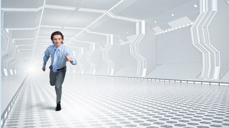 Young businessman running in futuristically designed tunnel