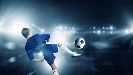 kicking ball: Rear view of kid boy in blue uniform on soccer stadium kicking ball