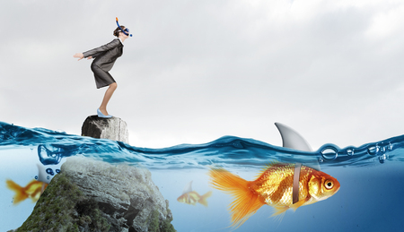 goldfish jump: Concept of fake threat when businesswoman jump in water with shark appear to be goldfish