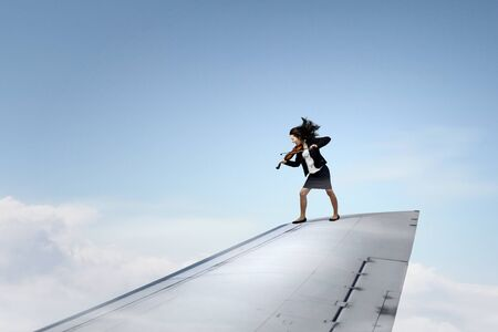 brink: Young businesswoman standing on edge of airplane wing and play violin