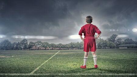 the uniform: Rear view of kid boy in red uniform on soccer field Stock Photo