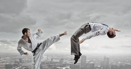 man power: Young determined karate man fighting with businessman in suit Stock Photo