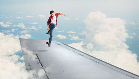 stunt: Skater boy doing stunt on edge of flying airplane Stock Photo