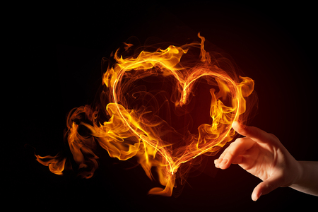 hands fire passion: Hand touch glowing love hearts symbol on dark background
