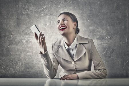 women laughing: Beautiful businesswoman with phone in hand sitting at table and laughs Stock Photo