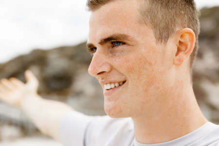outstretched arms: Young man in sport wear with outstretched arms standing on beach Stock Photo