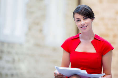 business life: Portrait of business woman in sitting outside and holding papers