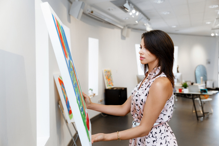 curiosity: Young caucasian woman standing in an art gallery in front of painting displayed on white wall Stock Photo