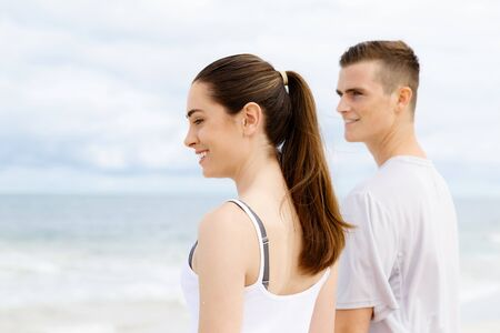 next to each other: Young couple looking thoughtful while standing next to each other on beach in sports wear