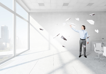 Young businessman in  modern office with paper plane in hand
