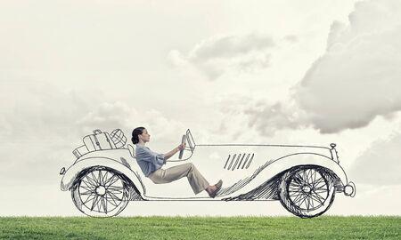 Young humorous woman driving drawn funny car