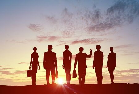 diferentes profesiones: Silhouette of business people of different professions on sunset background