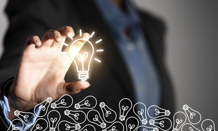 constructive: Close up of businesswoman taking glowing light bulb with fingers