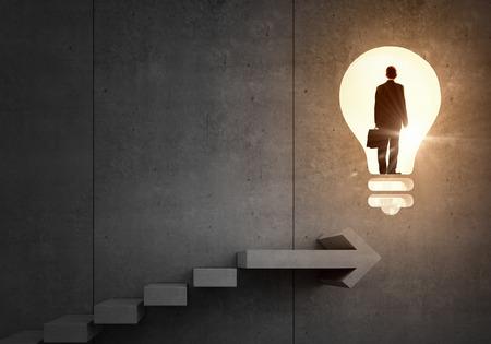 はしごと大きなアイデア電球の上に立っての実業家の背面図
