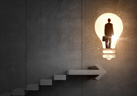 Back view of businessman standing on ladder and big idea bulb
