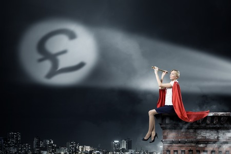 moneymaking: Young woman super hero and pound sign in spotlight