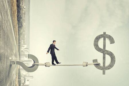 Young businessman walking on rope between question and dollar sign