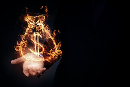 signos de pesos: Burning dollar sign in businessman palm on dark background Foto de archivo