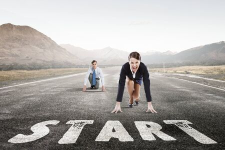 Young determined businesswoman and businessman standing in start position Stock Photo