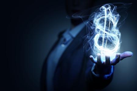 glowing: Burning dollar sign in businesswoman palm on dark background