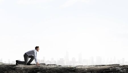 Young businessman standing in start position ready to compete