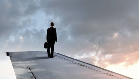 brink: Young businessman standing on edge of airplane wing