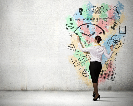 back in time: Back view of businesswoman drawing time management concept on wall