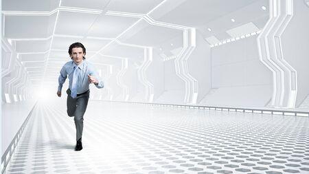 futuristically: Young businessman running in futuristically designed tunnel
