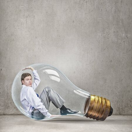 are trapped: Young thoughtful businessman trapped inside of light bulb