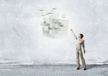 reaching hand: Businesswoman reaching hand to touch digital cube figure Stock Photo