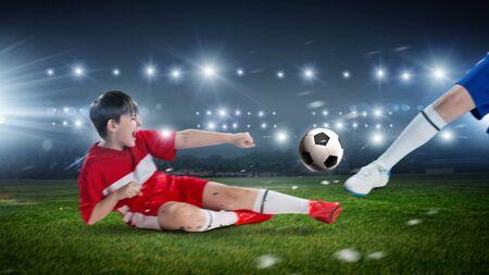 kicking ball: Kid boy in red uniform on soccer stadium kicking ball