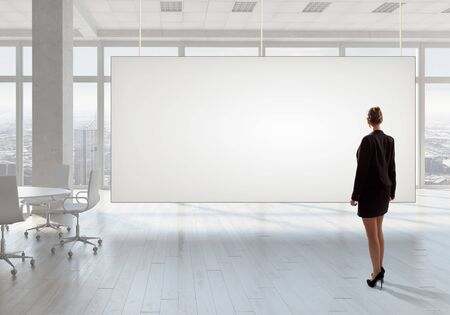 view of an elegant office: Elegant businesswoman in modern office interior against window panoramic view looking at blank banner