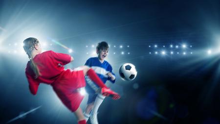 action girl: Kid boy and girl on soccer stadium fighting for ball